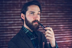 Handsome man with smoking pipe looking away Royalty Free Stock Images