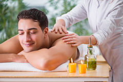 The handsome man during spa massaging session Stock Photos