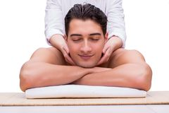 The handsome man during spa massaging session Stock Photography