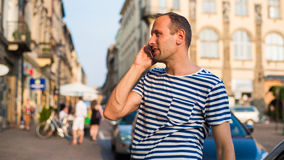 Handsome man speaking on the phone on city background. Stock Image