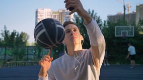 Handsome man spinning basketball on finger and taking selfie or having video chat, wearing earphones, smiling, park in