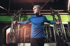 Handsome man in sportswear exercising at gym. Young handsome man in sportswear exercising at gym Royalty Free Stock Photography