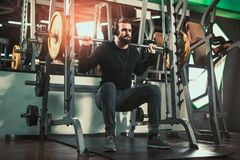 Handsome man in sportswear exercising at gym. Young handsome man in sportswear exercising at gym Stock Photography