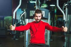 Handsome man in sportswear exercising at gym. Young handsome man in sportswear exercising at gym Stock Images
