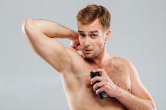 Handsome man spraying deodorant and looking at camera Royalty Free Stock Photos