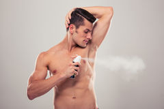 Handsome man spraying deodorant Stock Photo