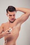 Handsome man spraying deodorant Royalty Free Stock Photography