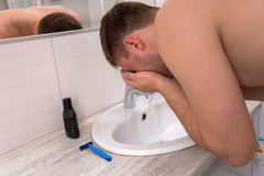 Handsome man spraying water on his face in the bathroom Royalty Free Stock Photo