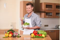 Handsome man squeezing lime for fresh salad. Stock Images