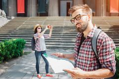 Handsome man stand outside and smile a bit. He holds map in hands. Young female tourist stands on back and takes stock image