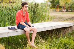 Handsome man standing on a bridge by the lake royalty free stock photography