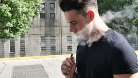 Man smoking ecig in street stock video footage
