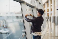 Handsome man standing beside glass wall in modern airport terminal, taking photo picture of airplane aircraft Royalty Free Stock Image
