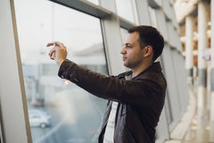 Handsome man standing beside glass wall in modern airport terminal, taking photo picture of airplane aircraft Stock Image