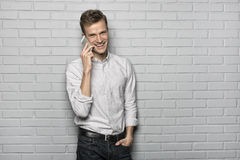 Handsome man standing on Grey wall background, on phone Stock Photo