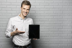 Handsome man standing on Grey wall background,Whith Tablet Pc Royalty Free Stock Photography