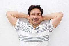 Handsome man standing with hands behind his head on white background stock photography