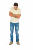 Handsome man standing looking down with arm crossed Royalty Free Stock Image