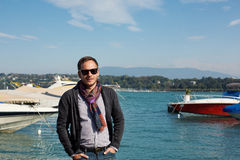 Handsome man standing near the lake with yachts on background Royalty Free Stock Photos