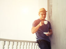Handsome man standing out of home lean on the balcony drinking c. Man standing out of home lean on the balcony drinking coffee in the morning Royalty Free Stock Images