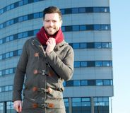 Handsome man standing outside city building with jacket and scarf Royalty Free Stock Photos
