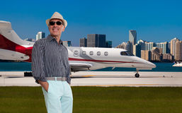 Handsome man standing outside a private jet Stock Photos