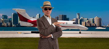 Handsome man standing outside a private jet. Wearing a hat Royalty Free Stock Image