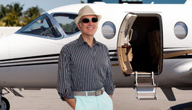 Handsome man standing outside a private jet stock images