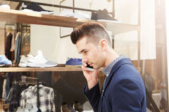 Handsome man standing outside store window on phone call royalty free stock images