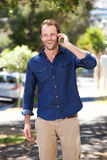 Handsome man standing outside talking on cell phone Royalty Free Stock Photo
