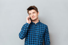 Handsome man standing over grey wall and talking by phone. Picture of handsome young man standing over grey wall and talking by phone. Looking aside stock photo