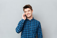 Handsome man standing over grey wall and talking by phone. Picture of handsome young man standing over grey wall and talking by phone. Looking aside stock photography