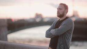 Handsome man standing on a quay, folding his arms on a chest. Man with a beard turns his head to camera and smiles. Blurred cars on the background stock footage