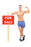 Handsome man standing by a for sale sign Stock Photography