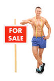 Handsome man standing by a for sale sign Royalty Free Stock Image