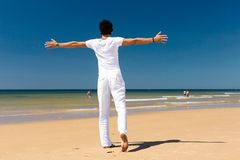 Handsome man standing in the sun on beach Stock Image