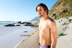 Handsome man standing with surfboard by the ocean Stock Image