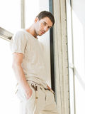 Handsome man standing on the windowsill Stock Photo