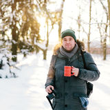 Handsome man standing in a winter forest Stock Image