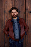 Handsome man stands against the backdrop of a wooden fence. Portrait of stylish hipster man with beard posing on beautiful wooden door background stock images