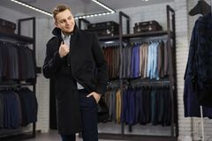 Handsome man stands in suit shop fashionable rich male dressed in expensive clothes posing indoors. Handsome young man in classic vest against row of suits in stock photography