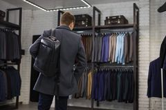 Handsome man stands in suit shop fashionable rich male dressed in expensive clothes posing indoors royalty free stock images
