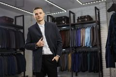 Handsome man stands in suit shop fashionable rich male dressed in expensive clothes posing indoors royalty free stock photos