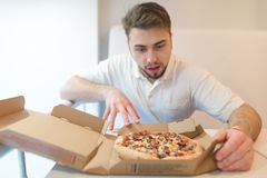 A handsome man stares at the pizza with a hungry look. The man is going to take a piece of pizza. royalty free stock photography