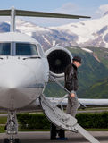 Handsome man on the steps of a private jet. Handsome fashinable man on the steps of a private jet Stock Images