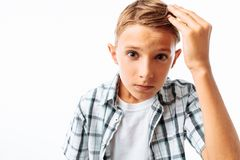Handsome man straightens his hair, teen boy changes hairstyle, in Studio on white background royalty free stock photo