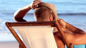 Handsome man with a straw hat relaxing on a deck chair. On the beach stock video