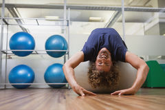 Handsome man stretching on fitness ball in gym Stock Image