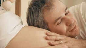 Handsome man stroking pregnant wife`s belly stock video footage