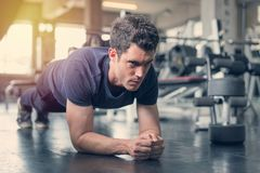 Handsome man and strong guy doing plank position exercise in fitness gym.  stock photos